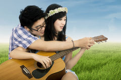 Romantic couple playing guitar at field Stock Photography