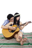 Romantic couple playing guitar on mat Royalty Free Stock Images