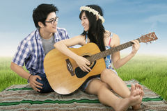 Romantic couple playing guitar together. Shooting outdoors Stock Image