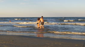 Romantic couple playing and teasing one another in the sea at the beach stock video footage
