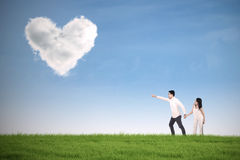 Romantic couple pointing at heart Stock Photo