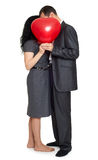 Romantic couple with read balloon of heart shape, dressed in black suit, isolated white Stock Image