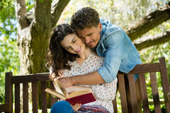 Romantic couple reading book on bench in garden. On a sunny day stock photography