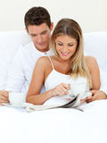 Romantic couple reading a newspaper Stock Images