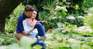 Romantic couple reading novel in park. During summer stock video footage