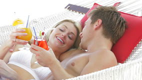Romantic Couple Relaxing In Beach Hammock With Cocktails. Romantic couple in hammock drinking cocktails and toasting one another.Shot on Canon 5d Mk2 with a stock video footage