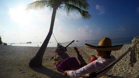 Romantic Couple Relaxing In Beach Hammock. Lukas and Dorota relaxing in Maldives, Kuredu , tranquil morning stock video