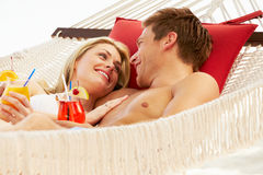 Romantic Couple Relaxing In Beach Hammock Stock Images