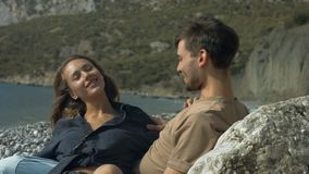 Romantic couple relaxing on the beach. Young couple in love sitting and hugging on the beach stock video footage