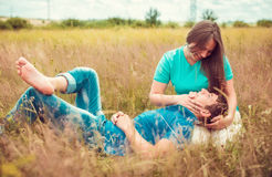 Romantic couple relaxing in field Stock Photos