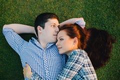 Romantic couple relaxing on grass Stock Photos