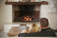 Romantic Couple Relaxing In Lounge Next To Open Fire stock photography
