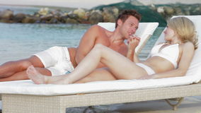 Romantic Couple Relaxing On Loungers At Beach stock video footage