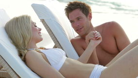 Romantic Couple Relaxing On Loungers At Beach stock footage