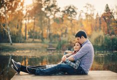 Romantic couple relaxing on the river dock in Stock Photos