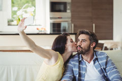 Romantic couple relaxing on sofa and taking a selfie Royalty Free Stock Photos