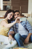 Romantic couple relaxing on sofa and taking a selfie Stock Image
