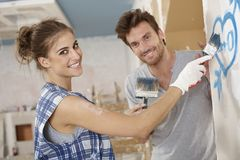Romantic couple renovating house. Painting heart on wall, smiling happy Royalty Free Stock Image