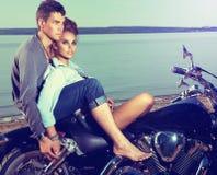 Romantic couple resting on lake shore, motorbike. Beautiful couple family sitting on lake shore on motor bike Royalty Free Stock Photo
