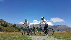 Romantic couple riding bicycle in beautiful landscape. Couple enjoys beautiful countryside scenery in New Zealand. Romantic couple riding bicycle Active stock image