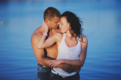Romantic couple in river during sunset Stock Photos