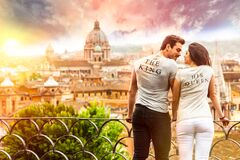 Romantic couple in Rome, Italy. A men and a women, they are looking at each other. On a terrace with railing overlooking Rome at