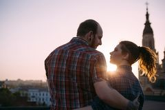Romantic couple on roof in focus on foreground. Cuddling people together enjoying sunset. Sensitive look, stylish hipsters, urban background with free space Royalty Free Stock Photography