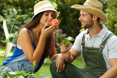 Romantic couple with rose. Romantic couple gardening, smelling rose at summertime, smiling Stock Image