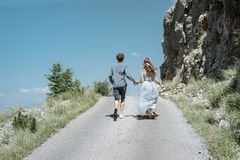 Romantic couple running along the road against the background o. F the mountains. Slow motion stock photo