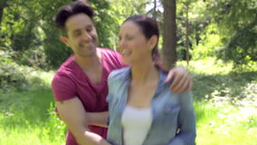 Romantic Couple Running Along Summer Woodland Path Together. Camera tracks happy couple as they run along leafy summer woodland path smiling and talking.Shot on stock video