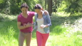 Romantic Couple Running Along Summer Woodland Path Together. Camera tracks happy couple as they run along leafy summer woodland path smiling and talking.Shot on stock footage