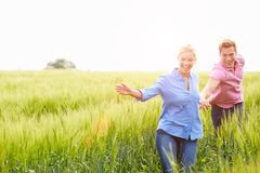 Romantic Couple Running In Field Holding Hands. Smiling Royalty Free Stock Images
