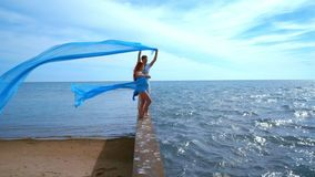Romantic couple. Sea holidays. Summer vacations. Pregnant couple. Holding blue cloth flying in wind. Love couple on pier. Romance. Happy couple in love relaxing stock footage