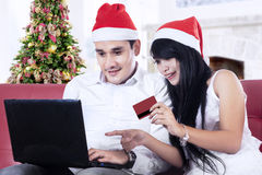 Romantic couple shopping online. Romantic couple buying christmas gift online with laptop at home Royalty Free Stock Image