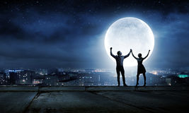 Romantic couple. Silhouettes of young romantic couple standing under the moon light Royalty Free Stock Photo