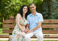 Romantic couple sit on bench in city park, summer season, adult happy people man and woman Royalty Free Stock Photo