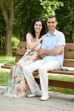 Romantic couple sit on bench in city park, summer season, adult happy people man and woman Royalty Free Stock Image