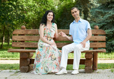Romantic couple sit on bench in city park, summer season, adult happy people man and woman Royalty Free Stock Photos