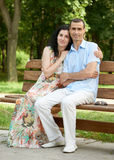 Romantic couple sit on bench in city park, summer season, adult happy people man and woman Stock Photography