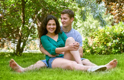 Romantic couple sit on grass in city park, summer season, lovers boy and girl Royalty Free Stock Photos