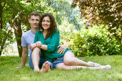 Romantic couple sit on grass in city park, summer season, lovers boy and girl Stock Photo