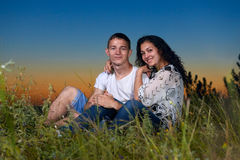 Romantic couple sit on grass at sunset on outdoor, beautiful landscape and dark night sky sky, love tenderness concept, young adul Stock Photography