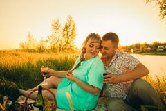 Romantic couple sit and kissing on background summer lake Stock Images