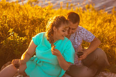 Romantic couple sit and kissing on background summer lake Royalty Free Stock Images