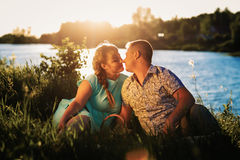 Romantic couple sit and kissing on background summer lake Stock Image