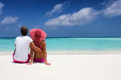Romantic couple sits hugging on a tropical beach Stock Images