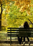 Romantic couple sitting in the autumn park Stock Photos