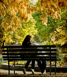 Romantic couple sitting in the autumn park Royalty Free Stock Images
