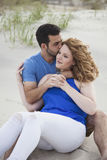 Romantic couple sitting on beach Stock Photography