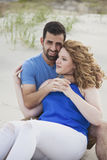 Romantic couple sitting on beach Royalty Free Stock Photography